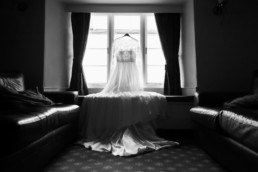 White weeding boho dress on a window in lake district