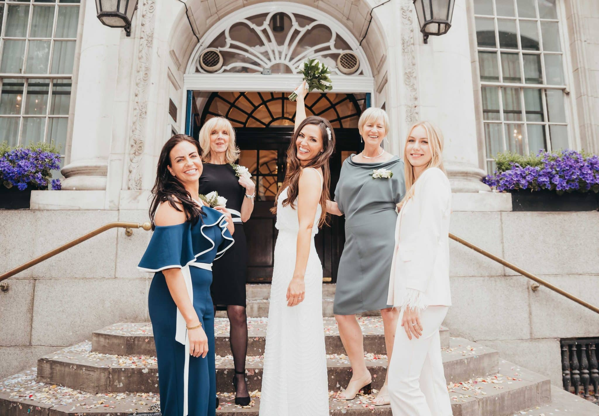 Married couple at the registry office, bride and the bridesmaids with the bouquet,