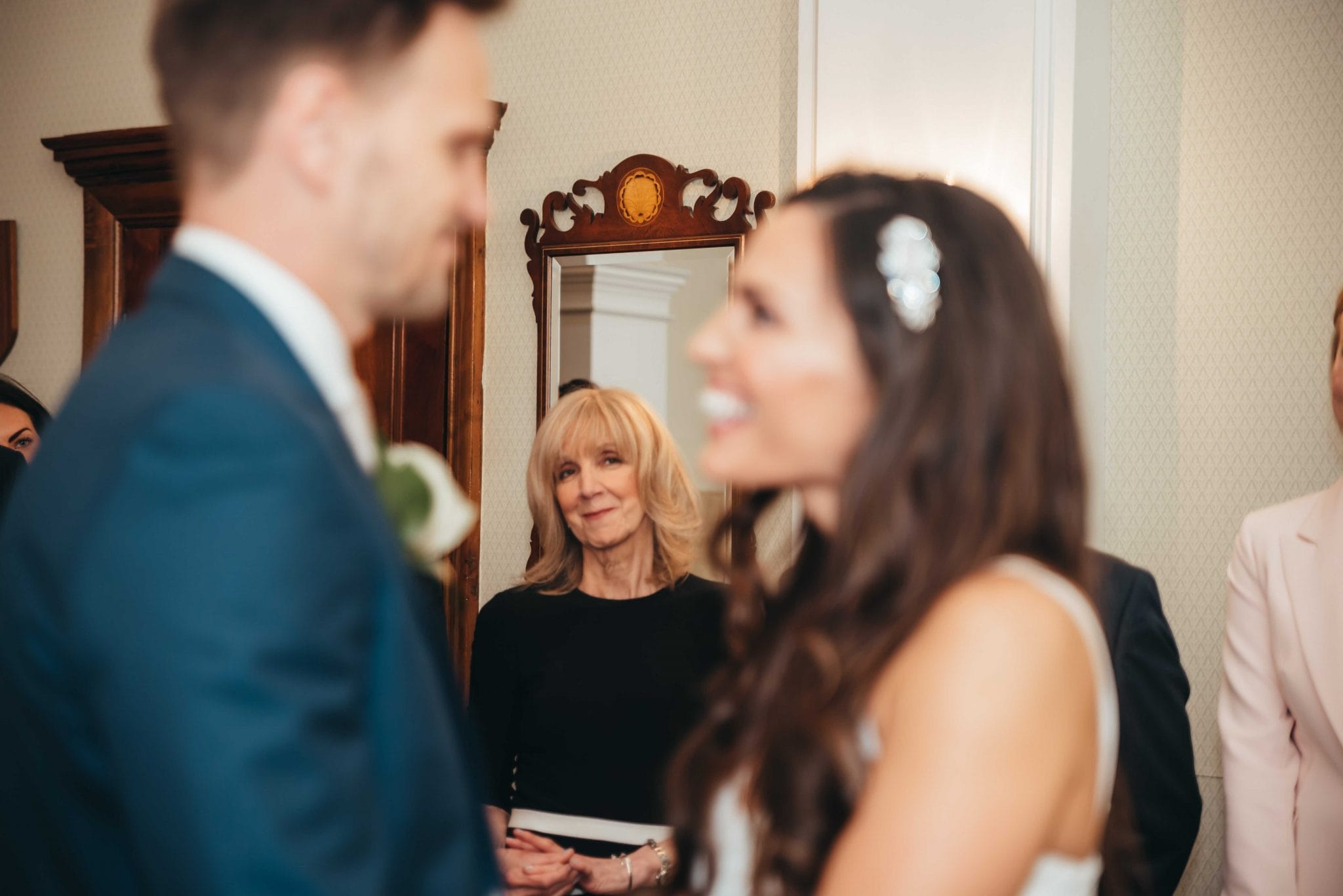 Married couple at the registry office, mother of the bride looking over during the vows