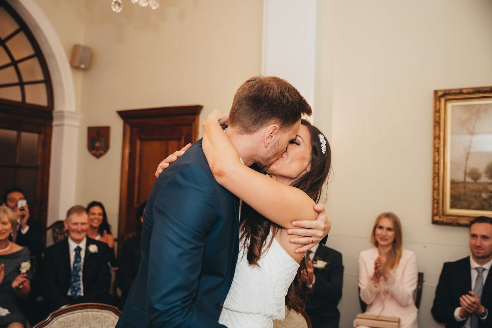 Married couple kissing after the vows at the registry office