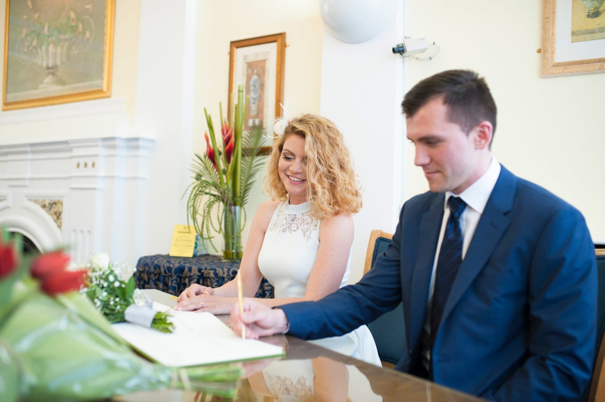 bride and groom Bromley on Bow Registry office, London UK Wedding photography ceremony room with the guest, register signing