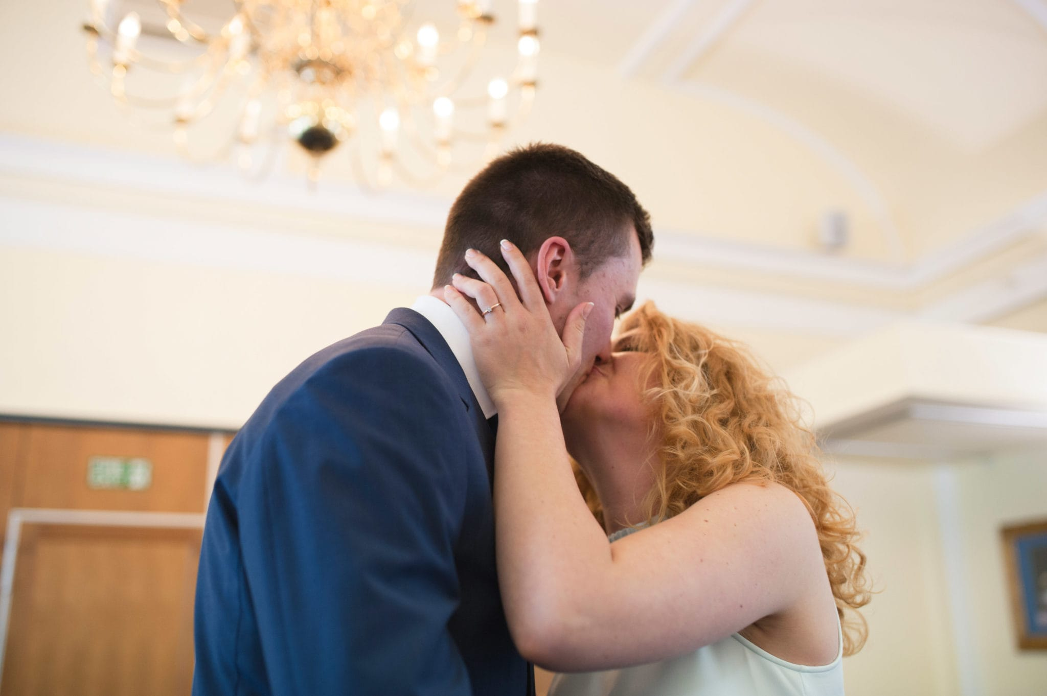 bride and groom Bromley on Bow Registry office, London UK Wedding photography ceremony room with the guest , first kiss