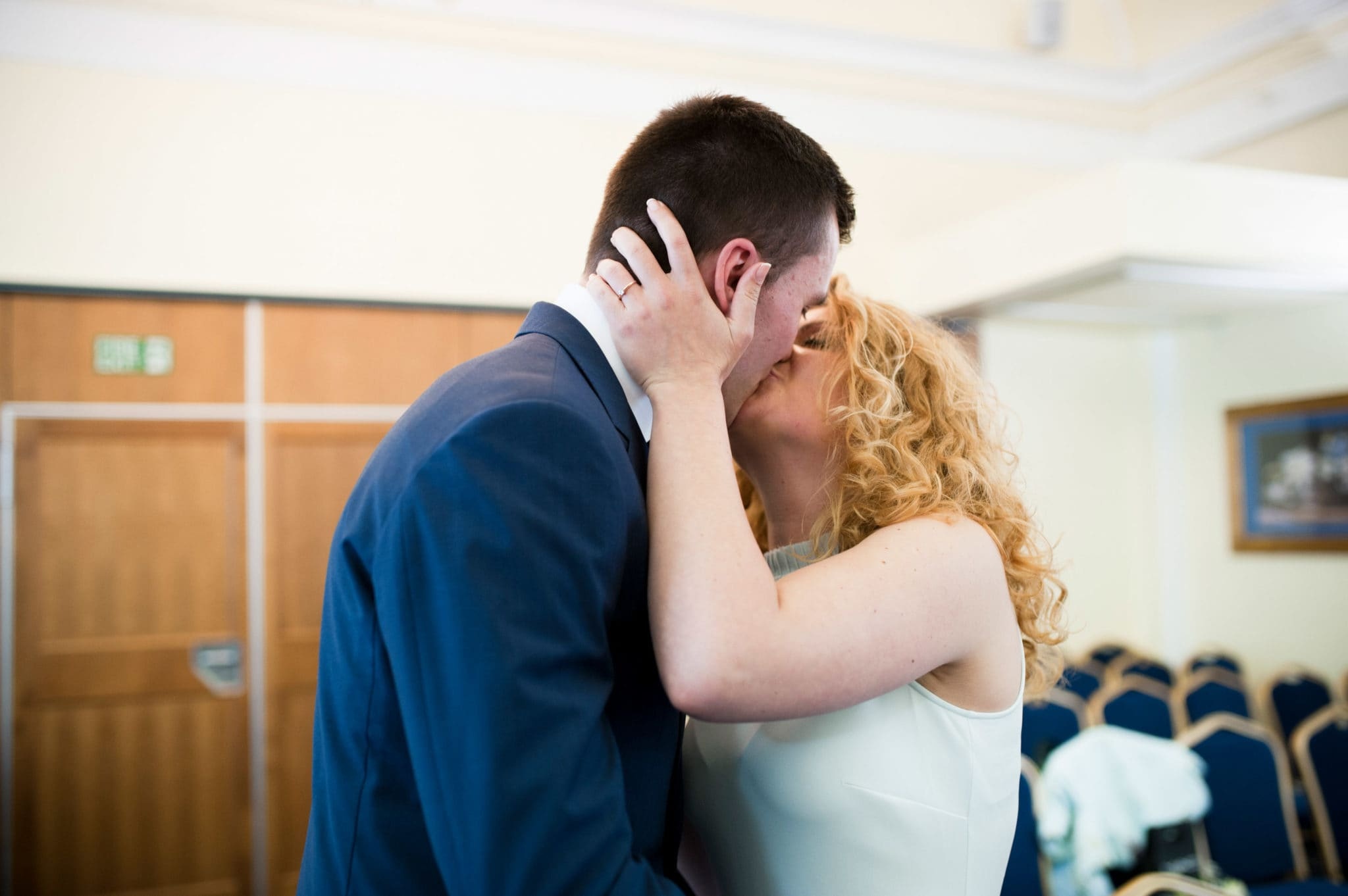 bride and groom Bromley on Bow Registry office, London UK Wedding photography ceremony room with the guest, first kiss