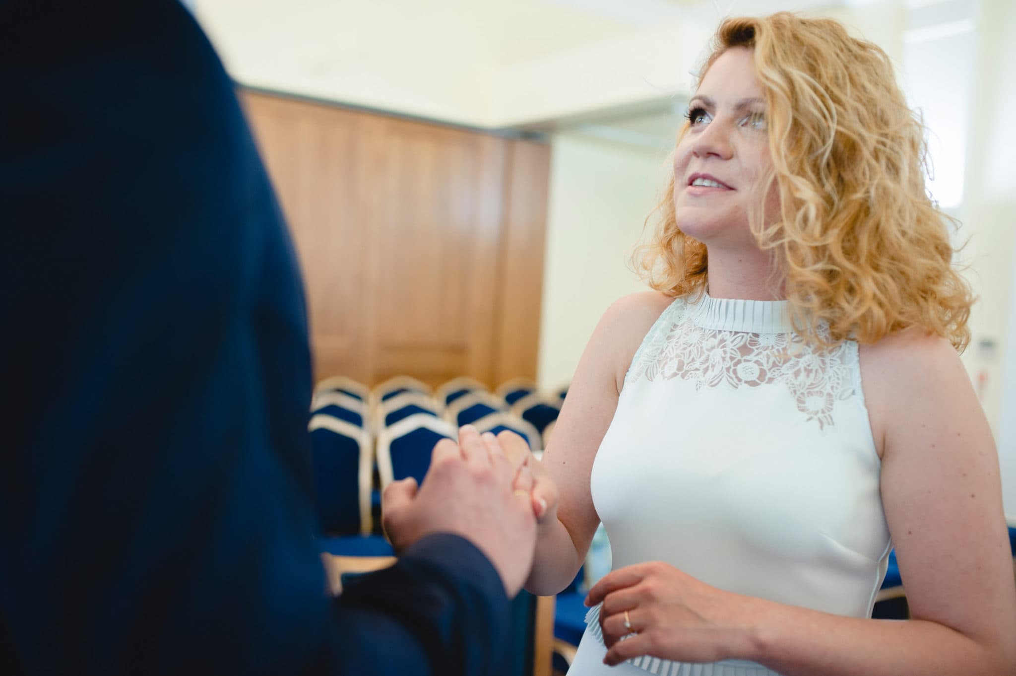bride and groom Bromley on Bow Registry office, London UK Wedding photography ceremony room with the guest ring exchange