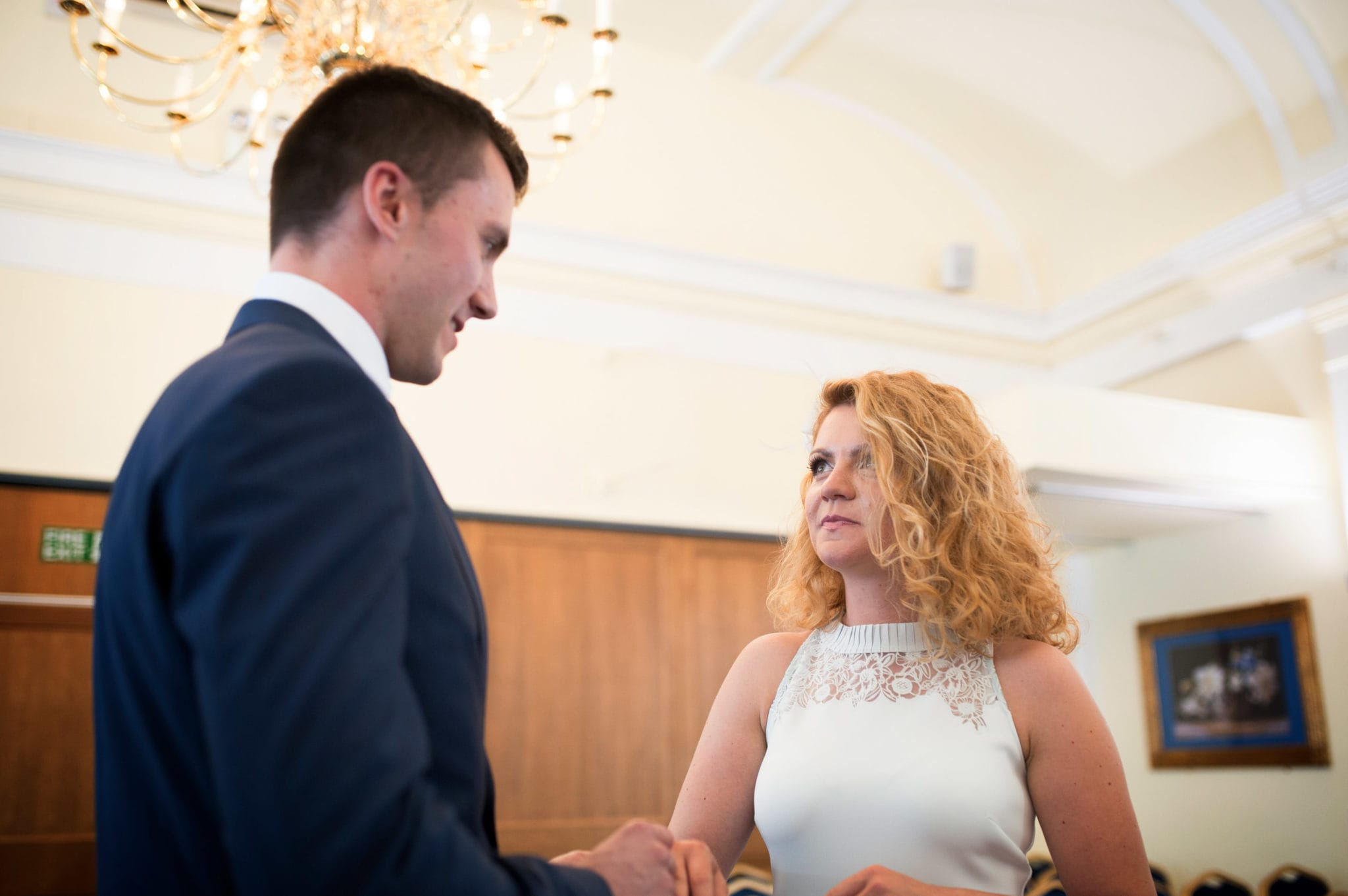 bride and groom Bromley on Bow Registry office, London UK Wedding photography ceremony room with the guest , ring exchange