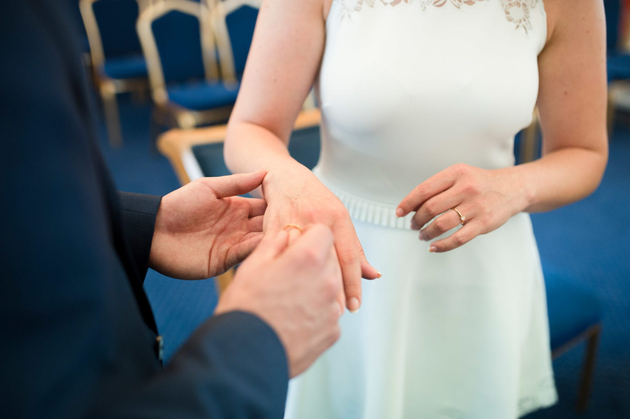 bride and groom Bromley on Bow Registry office, London UK Wedding photography ceremony room with the guest. ring echange