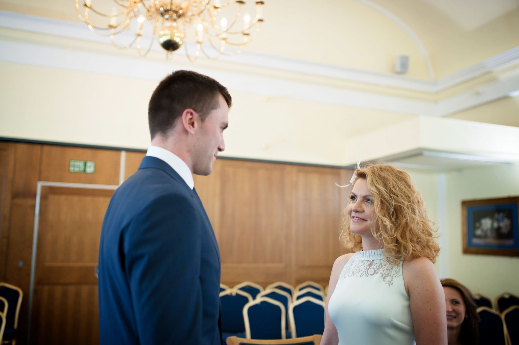 groon saying his vows Bromley on Bow Registry office, London UK Wedding photography ceremony room wioth the guest