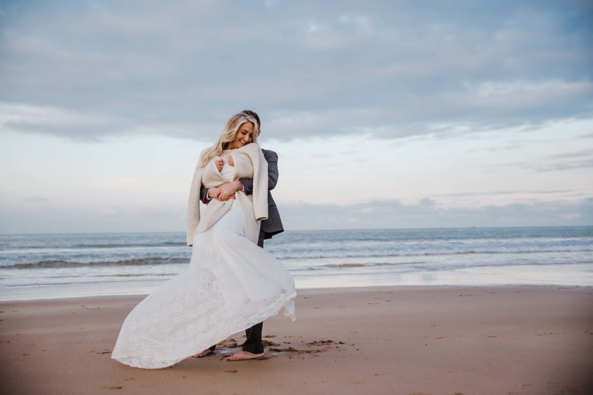 Wedding, bride, and groom walking at the beach . Wedding photographer london
