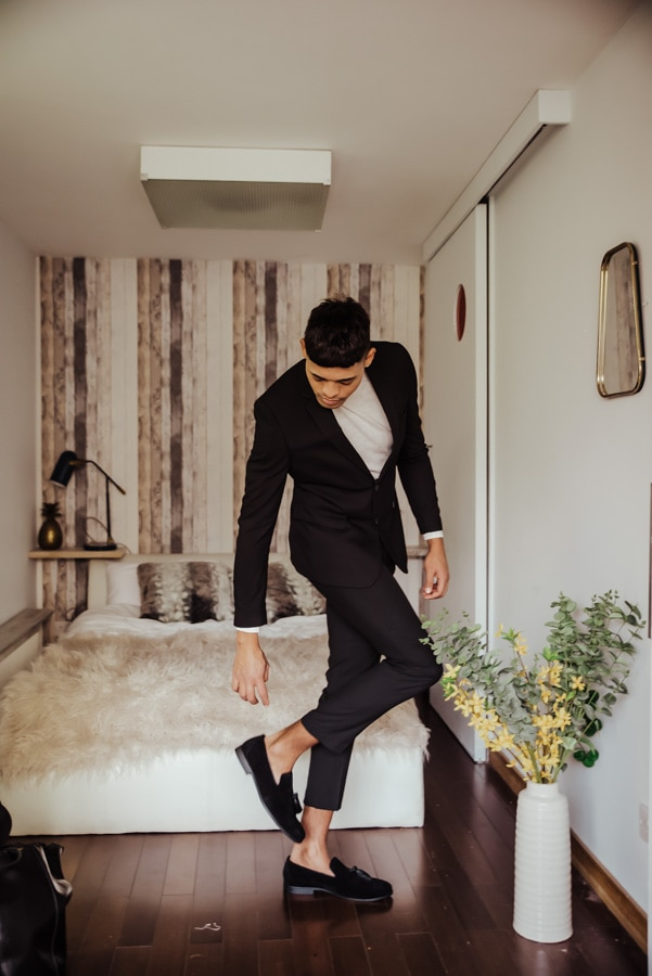 Groom wearing balck suit and white trutle neck,