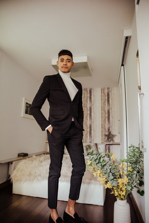 Groom ready to go, wearing balck turtle neck and coat, black trousers
