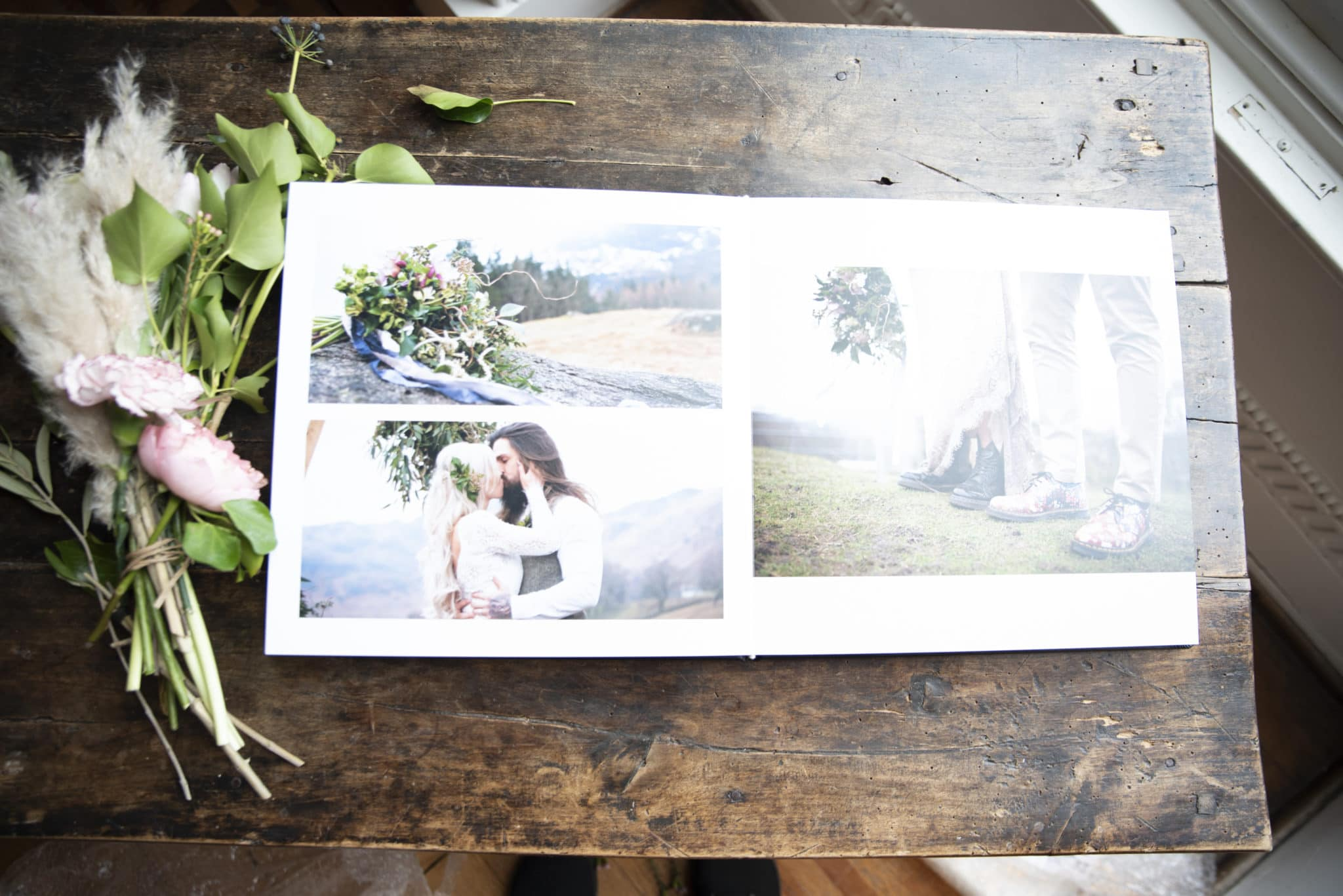 Wedding Photography Album on a wooden table with flowers ont he side
