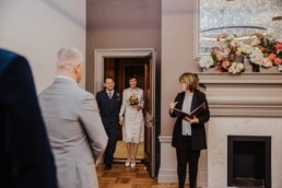 Katya in silk vintage weddign dress, Brett in blue suit at the Old Marylebone registry office London entracne of the bride in tje room