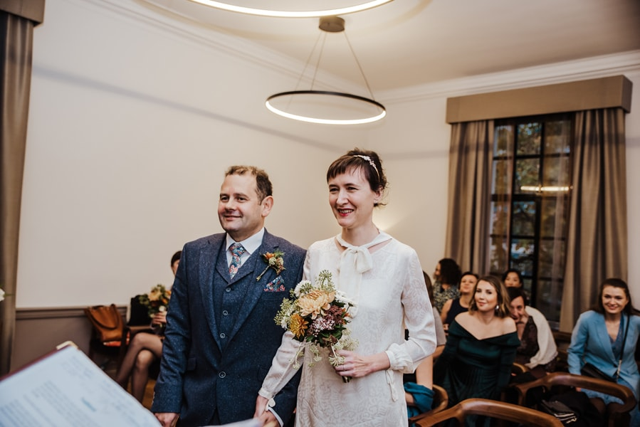 Katya in silk vintage weddign dress, Brett in blue suit at the Old Marylebone registry office London entracne of the bride in tje room