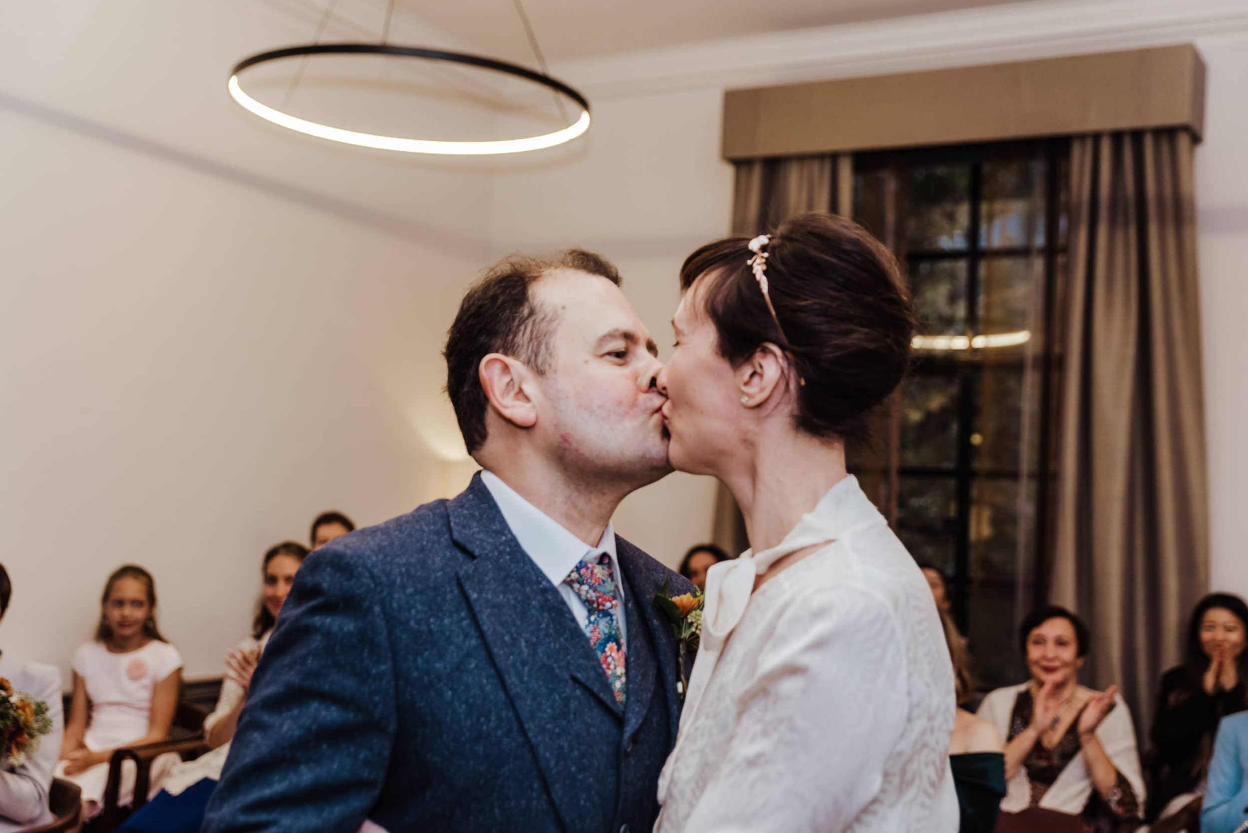 Katya in silk vintage weddign dress, Brett in blue suit at the Old Marylebone registry office london first kiss ceremony