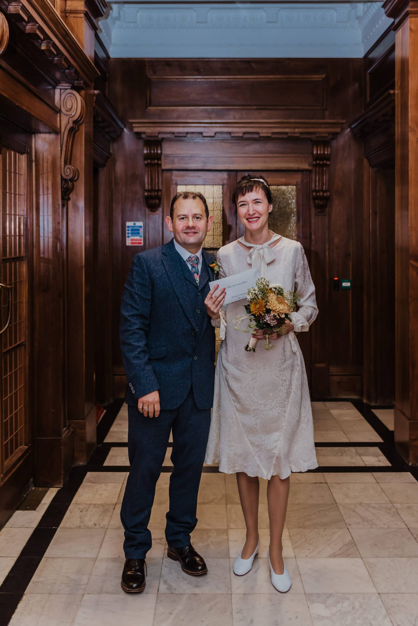 Katya in silk vintage weddign dress, Brett in blue suit at the Old Marylebone registry office London marriage certificate ceremony