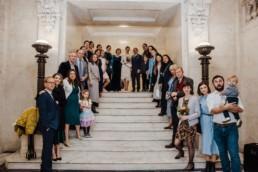 Katya in silk vintage weddign dress, Brett in blue suit at the Old Marylebone registry office London , group shot oat the steps inside
