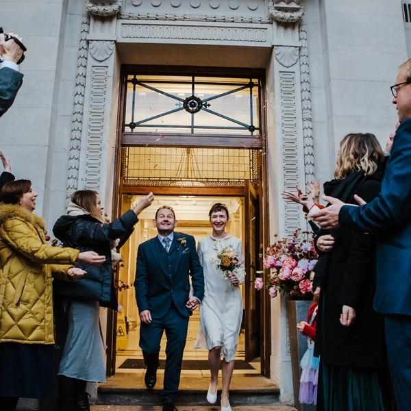 Katya in silk vintage weddign dress, Brett in blue suit at the Old Marylebone registry office London confetti shot