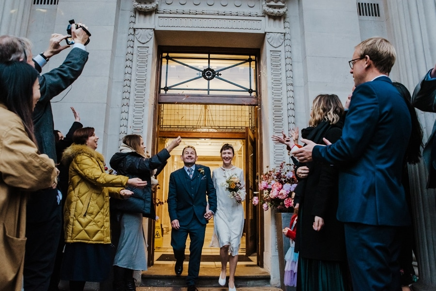 Katya in silk vintage weddign dress, Brett in blue suit at the Old Marylebone registry office London confetti shot