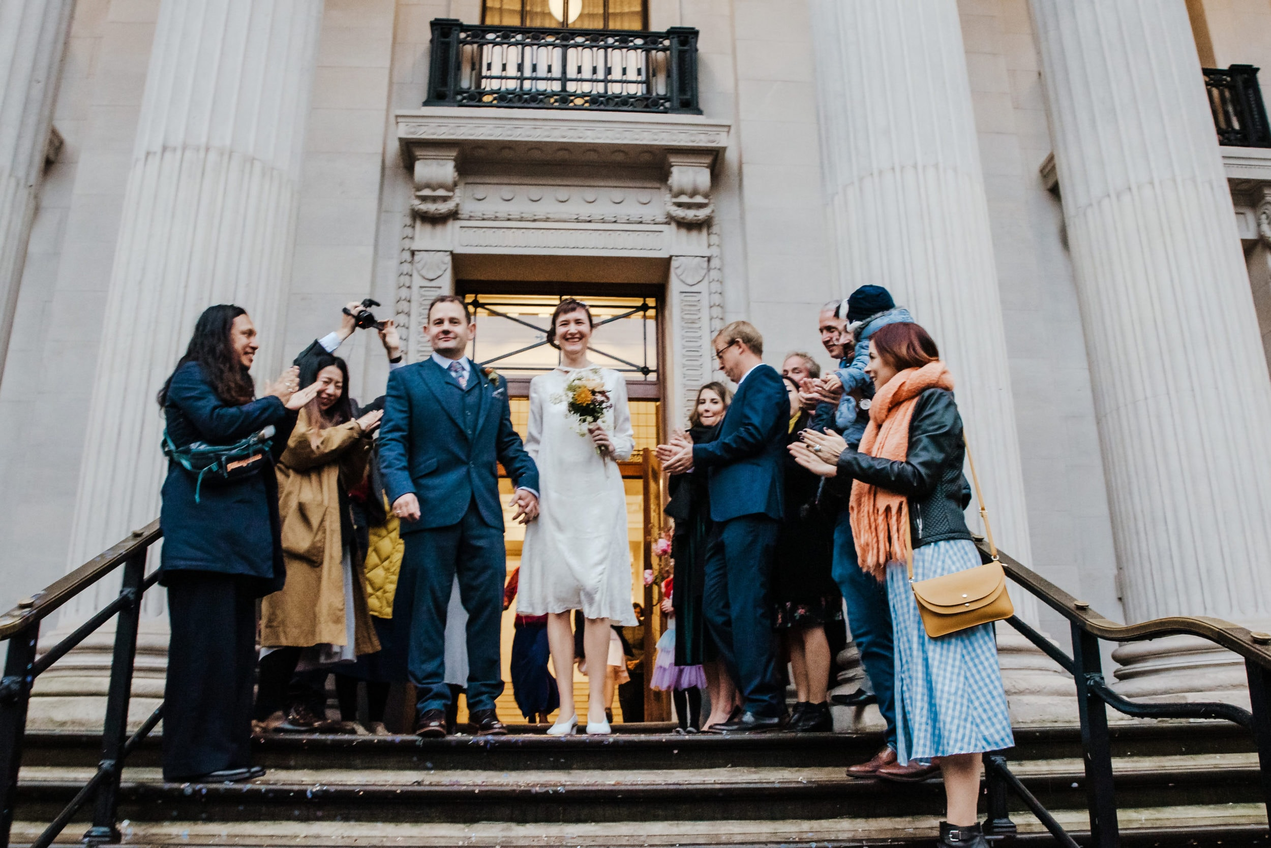 Katya in silk vintage weddign dress, Brett in blue suit at the Old Marylebone registry office London confetti throwing at the entrance