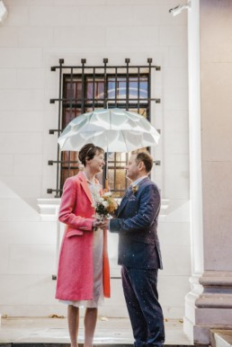Katya in silk vintage weddign dress, Brett in blue suit at the Old Marylebone registry office London couples shot at the entrance