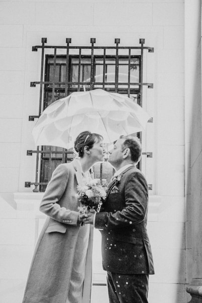 Katya in silk vintage weddign dress, Brett in blue suit at the Old Marylebone registry office London couples shot under and umbrella
