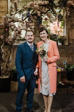 Katya in silk vintage weddign dress, Brett in blue suit at the Old Marylebone registry office London couples shot under and umbrella