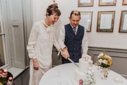 Katya in silk vintage wedding dress, Brett in blue suit at the Old Marylebone registry office London wedding celebrations at the pub