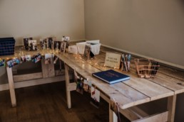 wedding guest book table with famiky photo fromaes on 3 generations and fairy lights Roshni photography The Milling Barn, Bluntswood Hall, Throcking wedding photographer