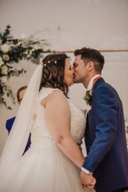 Groom and bride at the ceremony first kiss Roshni photography The Milling Barn, Bluntswood Hall, Throcking wedding photographer