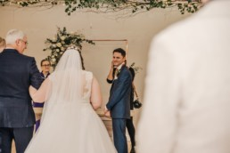 Wedding ceremony, bride in white walking down to the groom Roshni photography The Milling Barn, Bluntswood Hall, Throcking wedding photographer