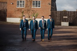 Groom and Groomsmen in blue suits outside the barn before the wedding Roshni photography The Milling Barn, Bluntswood Hall, Throcking wedding photographer