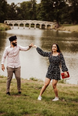 Couple holding hands near a river at the Painshill Park Surrey engagement shoot