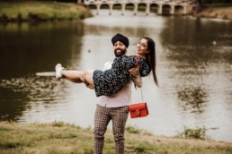 Fiance picking up his fiancé near a river at the Painshill Park Surrey engagement shoot