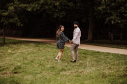 Couple looking back near a river at the Painshill Park Surrey engagement shoot