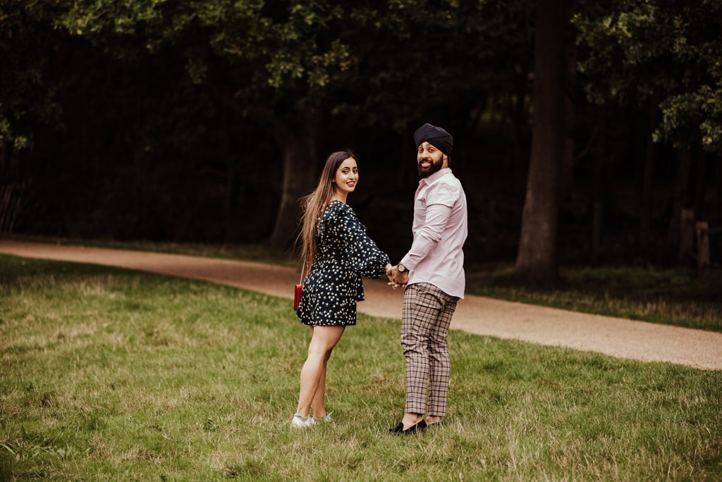 Couple looking back at the camera near a river at the Painshill Park Surrey engagement shoot