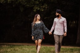 Couple holind hands and looking towards each other,near a river at the Painshill Park Surrey engagement shoot
