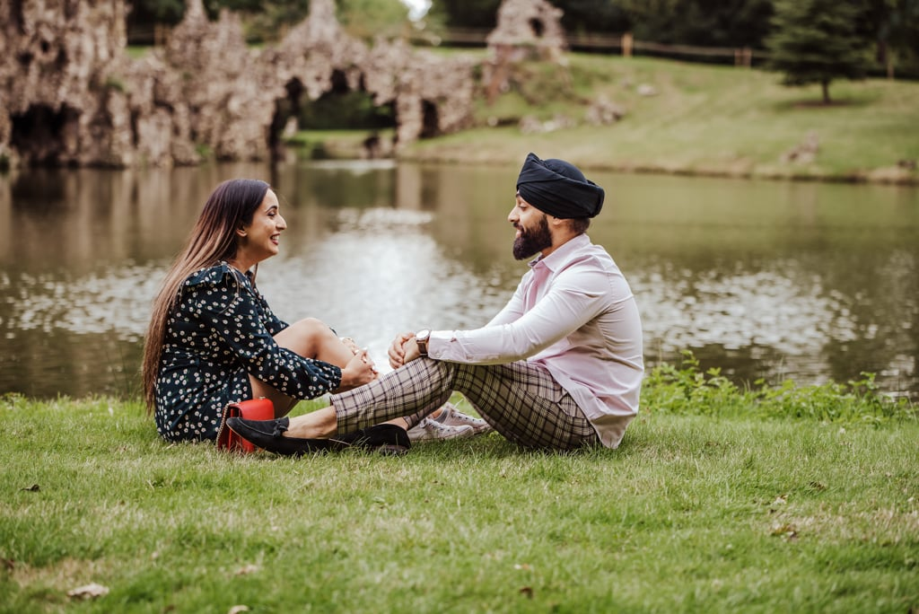 Couple sitting down and giggling near a river at the Painshill Park Surrey engagement shoot