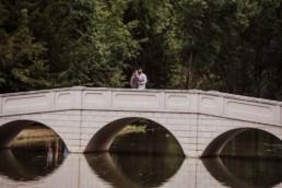 Couple at the bridge near a river at the Painshill Park Surrey engagement shoot