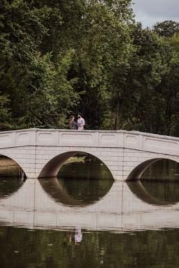 Couple on the bridge near a river at the Painshill Park Surrey engagement shootPainshill Park Surrey engagement shoot