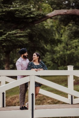 Couple on the bridge near a river at the Painshill Park Surrey engagement shoot