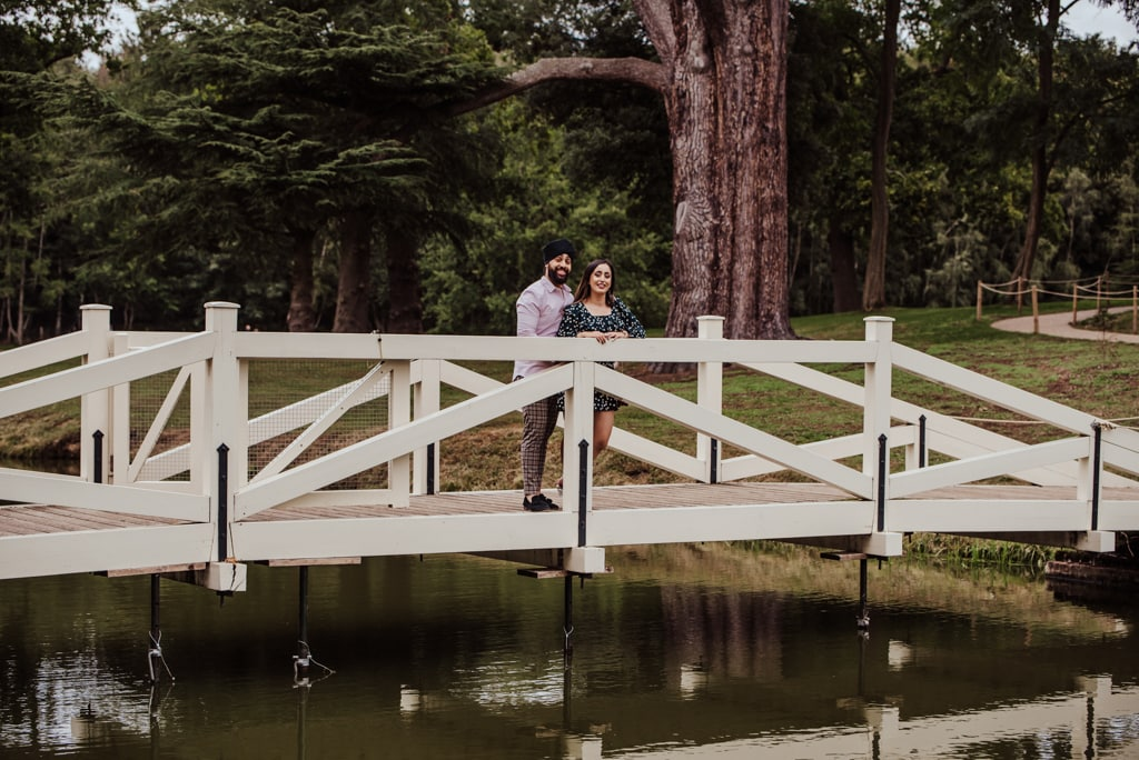 Couple hugging on the bridge near a river at the Painshill Park Surrey engagement shoot
