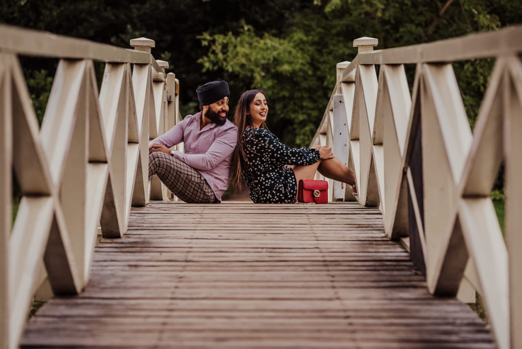 Couple sitting on the bridge back to back, looking at each other near a river at the Painshill Park Surrey engagement shoot
