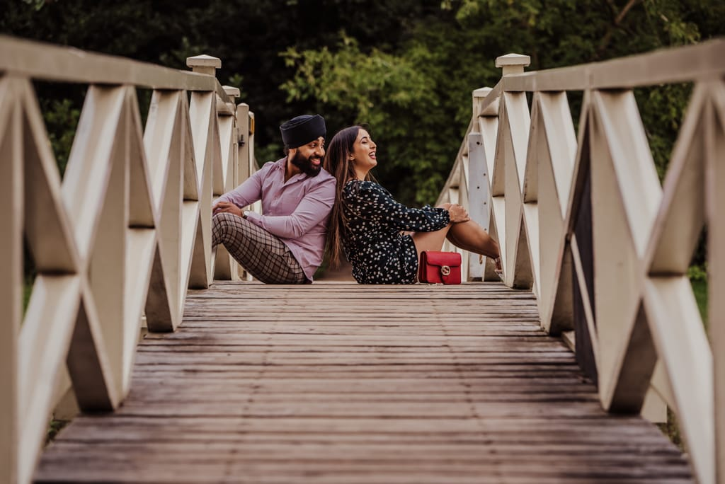 Couple sitting on the bridge and laughing near a river at the Painshill Park Surrey engagement shoot