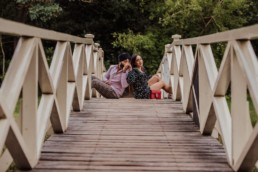 Couple sitting on the bridge near a river at the Painshill Park Surrey engagement shoot
