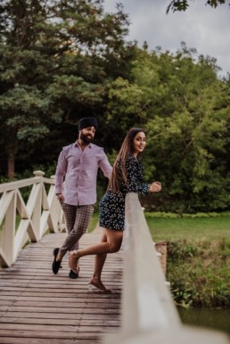 Couple standing on the bridge near a river at the Painshill Park Surrey engagement shoot