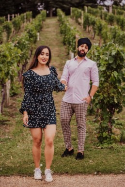 Couple walking through the vineyard near a river at the Painshill Park Surrey engagement shoot