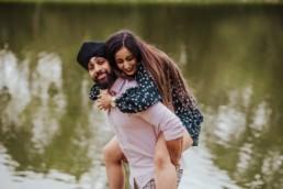 boyfriend piggy backing his girlfriend near a river at the Painshill Park Surrey engagement shoot