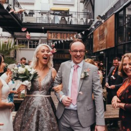 Bride nad groom exiting h the depot showered by confetti made of dried flowers by their friends and family